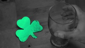 Hand putting down empty pint beside large green shamrock Royalty Free Stock Photography