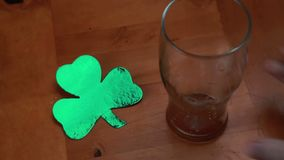Hand putting down empty pint beside large shamrock Royalty Free Stock Image