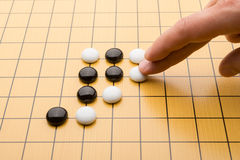 Hand putting down piece of GO Stock Image