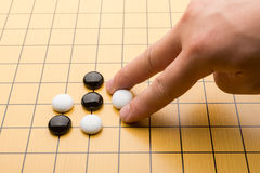Hand putting down piece of GO Royalty Free Stock Images