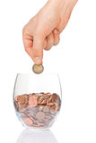 Hand putting 2 euro into glass with euro cents Stock Photo