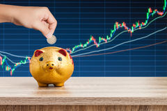 Hand putting 2 Euros coin into piggy bank with stock graph Royalty Free Stock Photography
