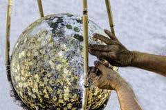 Hand putting gold leaf on boundary stone Royalty Free Stock Image