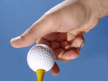 Hand Putting Golf Ball on Tee. View of a hand putting a golf ball on golf tee against a blue sky background Royalty Free Stock Image