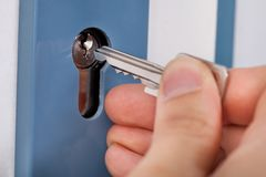 Hand Putting House Key Into Door Royalty Free Stock Images