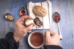 A hand putting jam on a piece of bread with blurred bread lying with jam in spoons around it in the background. Royalty Free Stock Image