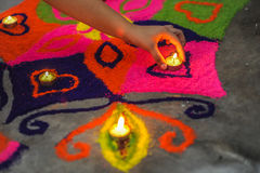 A hand putting a lamp on a beautiful and colorful rangoli on Diwali/Deepavali Celebration