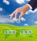 Hand putting letter c to  success word. On blue sky , business concept Royalty Free Stock Photo