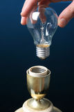 Hand putting a light bulb in a lamp. Concept of idea and solution royalty free stock image