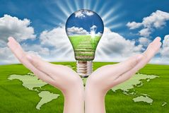 Hand putting light bulb for save world. Stock Image
