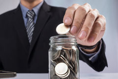 Hand putting mix coins and seed in clear bottle, Business invest Royalty Free Stock Photography