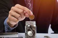 Hand putting mix coins and seed in clear bottle and copyspace, B Stock Image