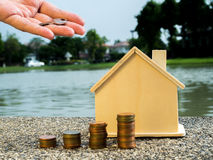 Hand putting money coins stack growing with house behind, saving money for home concept.  Stock Photos