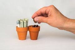 Hand putting money coins in a terracotta pot Stock Photo