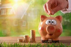 Hand putting money into piggy bank to buy a house Royalty Free Stock Photography