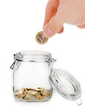 Hand putting one euro coi. N into money jar isolated on white Stock Photography