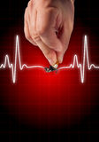 Hand putting out cigarette on heart beat line Stock Images