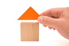 Hand putting a roof to make up a house with clipping path. Hand putting a roof to make up a house on white with clipping path Stock Image