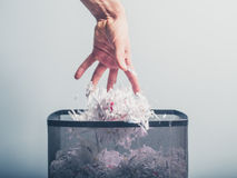Hand putting shredded paper in basket Royalty Free Stock Images