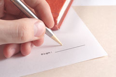Hand putting sign. Hand signing with steel pen Royalty Free Stock Photo