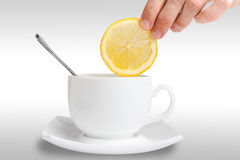 Hand putting a slice of lemon in cup of tea. Women hand putting a slice of lemon in cup of tea Royalty Free Stock Images