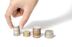Hand putting stack of coins Stock Images