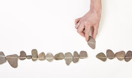 Hand putting stone in line Stock Photo