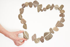 Hand putting stone in love heart Royalty Free Stock Photo