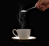 Hand putting sugar in coffee cup with smoke on black Royalty Free Stock Photos