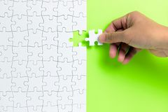 Free Hand Putting The Last Piece Of White Puzzle For Business Concept Or Content Background Stock Image - 145761461