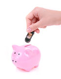 Hand is putting toy car into piggy bank Royalty Free Stock Image