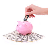 Hand is putting toy car into piggy bank Stock Images
