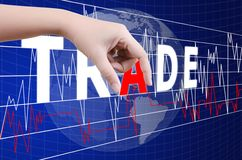 Hand putting Trade word on the stock market graph. Stock Images