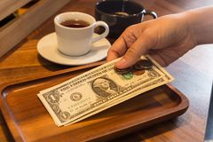 Hand putting US money tips in tray. Royalty Free Stock Images