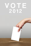 Hand putting a voting ballot in a slot of box Stock Photo