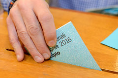 Hand putting a voting ballot in a slot of box Stock Image