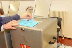 Hand putting a voting ballot in a slot of box Stock Photos