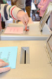Hand putting a voting ballot in a slot of box Stock Photography