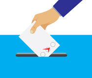 Hand putting voting paper in the ballot box. Stock Photos