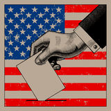 Hand putting voting paper on the USA flag background Royalty Free Stock Image