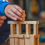 Hand putting Wood Building Block on a Constuction Royalty Free Stock Photo
