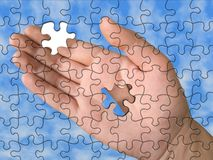Hand from puzzle without one piece. (it layz on palm), sky background Stock Photo