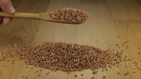 Hand quickly pours the buckwheat grains from a wooden spoon onto a pile of buckwheat. stock video