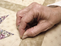 Hand Quilting. Female hand quilting a fabric quilt Stock Photos