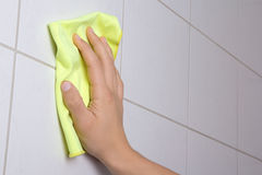 Hand with rag cleaning the bathroom tiles Royalty Free Stock Photo