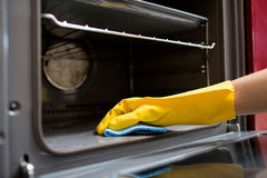 Hand with rag cleaning oven at home kitchen Royalty Free Stock Images