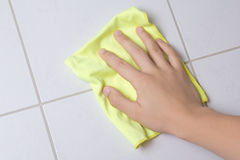 Hand with rag cleaning tile wall Royalty Free Stock Image