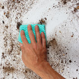 Hand with rag cleans very dirty surface Royalty Free Stock Photos
