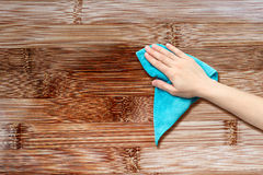 Hand with a rag. To dust the wood furniture Royalty Free Stock Image