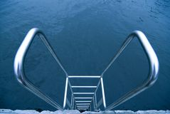 Hand-rails over water. Metallic stairs with hand-rails on the swimming pool water background Stock Photo